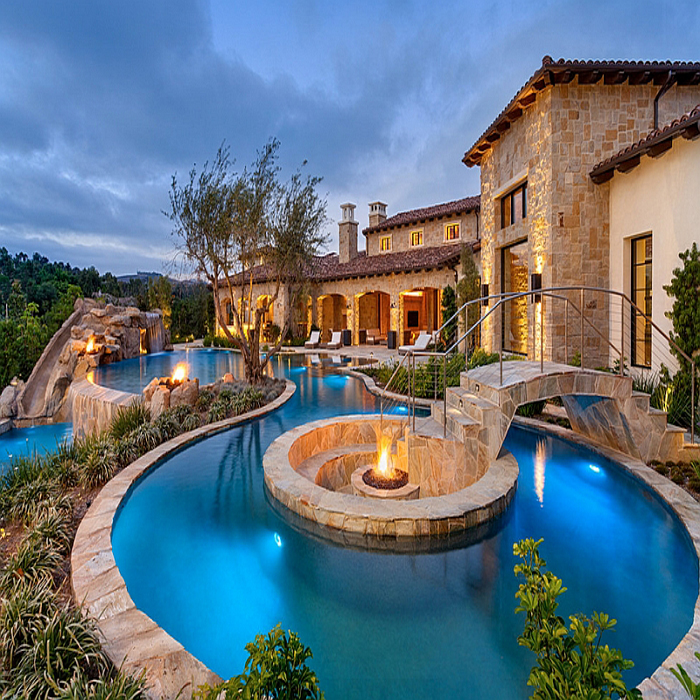 Fire-pit-at-the-heart-of-the-pool-with-sunken-seating-around-it-and-a-beautiful-bridge-leading-the-way